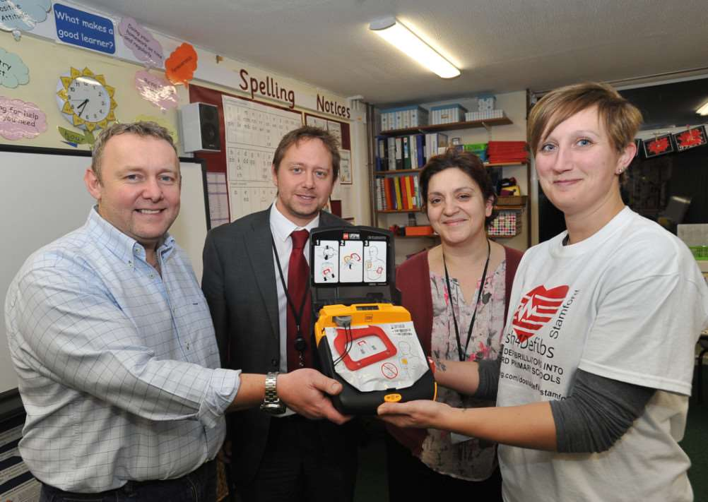 Steve Gaunt, chairman of the Malcolm Sargent primary academy PTFA, vice principal Tim Cox, Jo Seager , teaching assistant and Dannin Vincent from Dosh4Defibs at pres of machine to the school EMN-141012-202457009