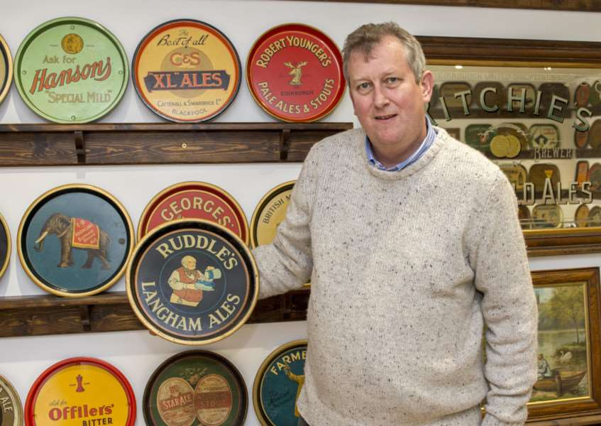 Richard Percival with his collection of nearly 1,300 brewery trays