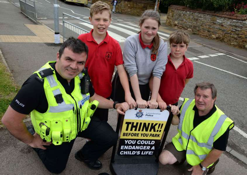 Police and pupils encourage parents to park responsibly outside Langham Primary School. PC Laurie Appleton with junior road safety officers Oliver Appleton, Ellie Brentnall and James Cockerill, and Ian Fraser. Photo: Alan Walters MSMP-08-06-15-aw002 EMN-150906-115738001