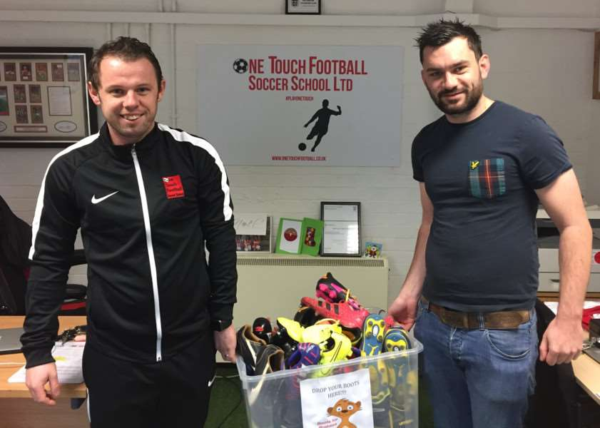 Glenn Vaughan, left, hands over some boots to Tom Berridge of Birch Wood Special School, in Melton Mowbray