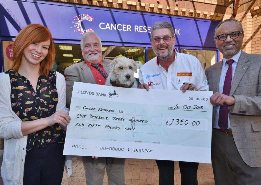 Cheque pres to Naomi Caddell, manager of the Cancer research shop in Bourne from Phil Wilson and his dog Jack with Martin Wolfie Adams and Jo Sunner, a local osteopath EMN-150210-175737009