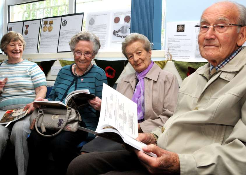 Elizabeth Noble, Nancy Titman, Dorothea and Albert Price find some family history in The Deepings Remember 1914 to 1918 book. Photo by Tim Wilson.