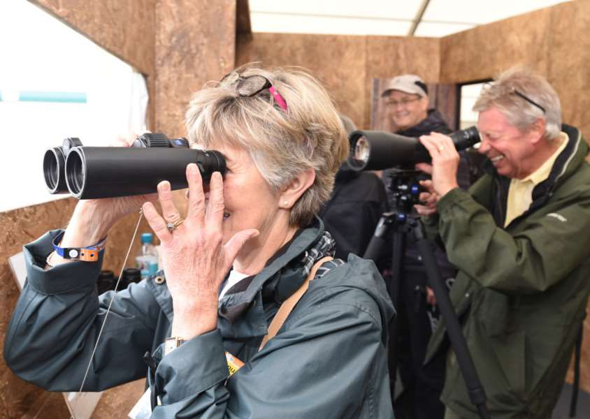 Birdfair 2016: Visitors in one of the hides looking at wildlife EMN-160819-164822009